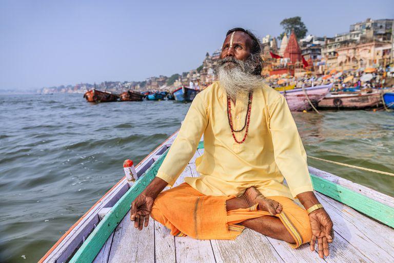 Sadhu is meditating in boat on Holy Ganges River, Varanasi