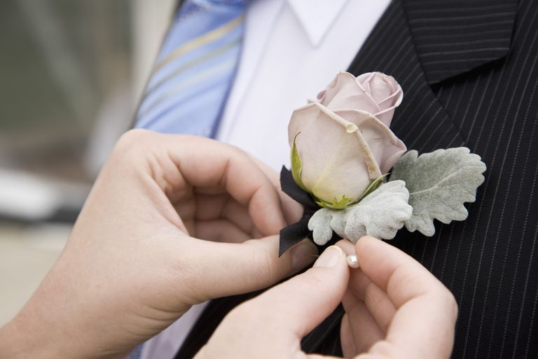 Detail of a woman pinning a corsage to a jacket lapel, Melbourne, Victoria, Australia