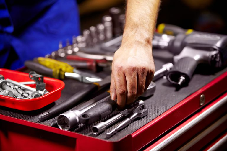 Cropped image of a man's hands grabbing a tool from his toolbox.