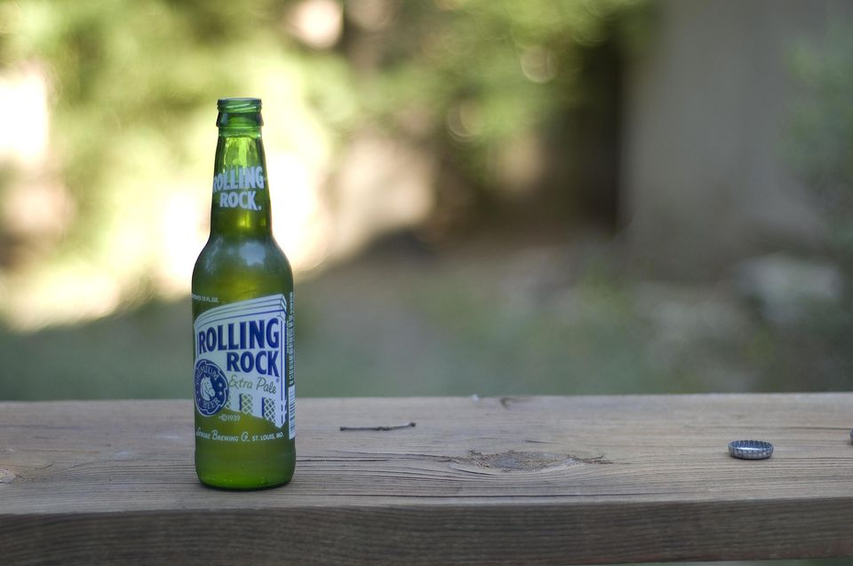 A bottle of Rolling Rock and its bottle cap