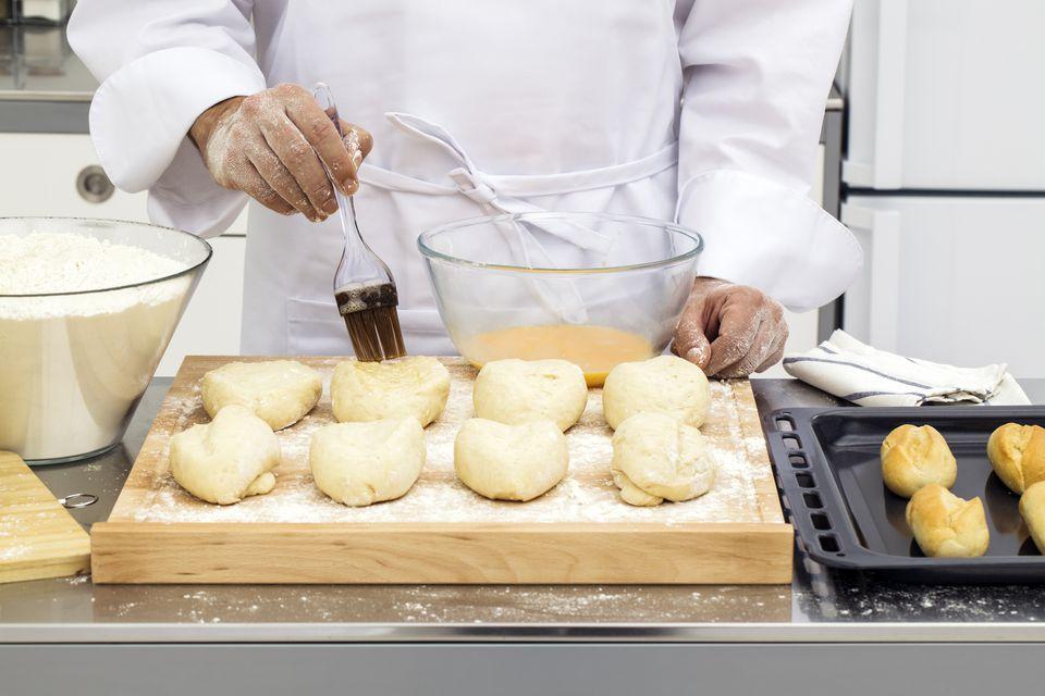 Brushing egg wash on bread