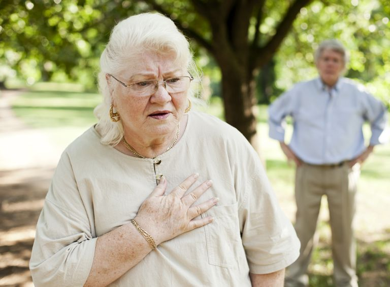senior woman with shortness of breath and chest pain, senior man in background