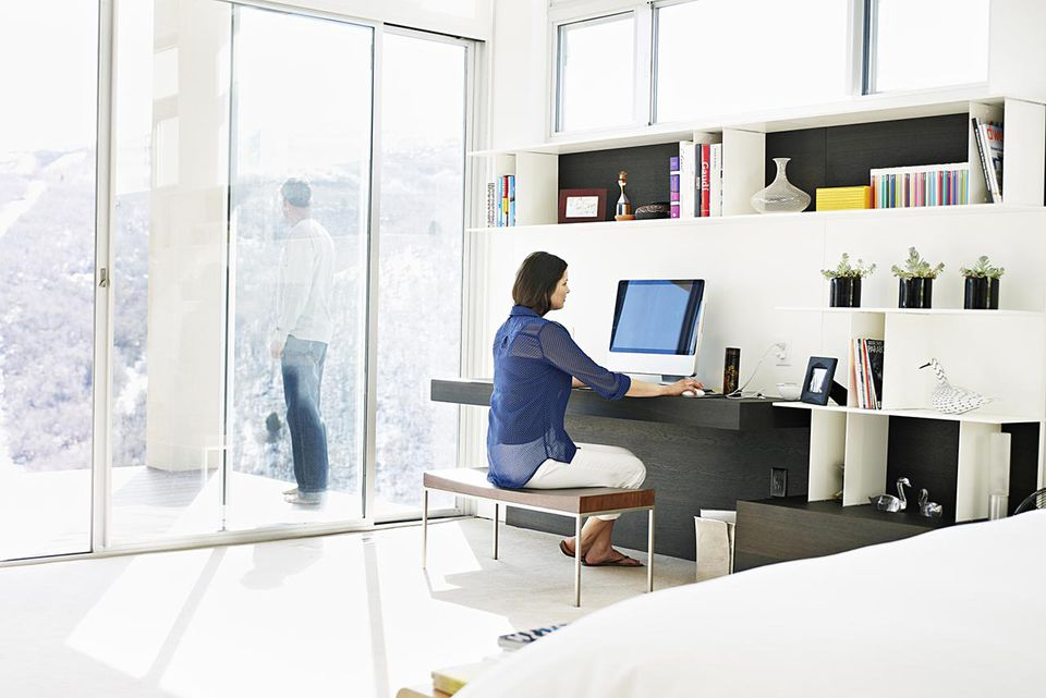 Woman sitting at desk in bedroom working on computer husband in background standing on deck looking out
