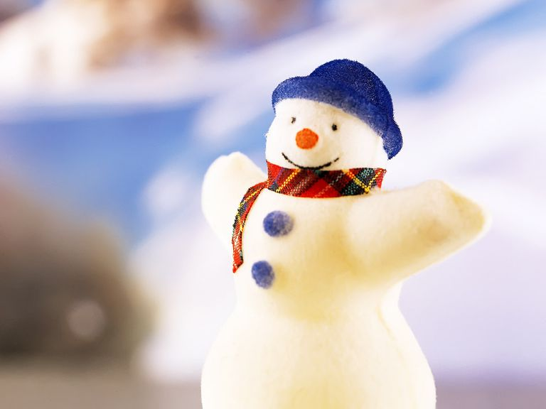 A snowman with a blue hat and plaid scarf