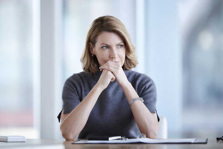 Pensive businesswoman looking away in conference room