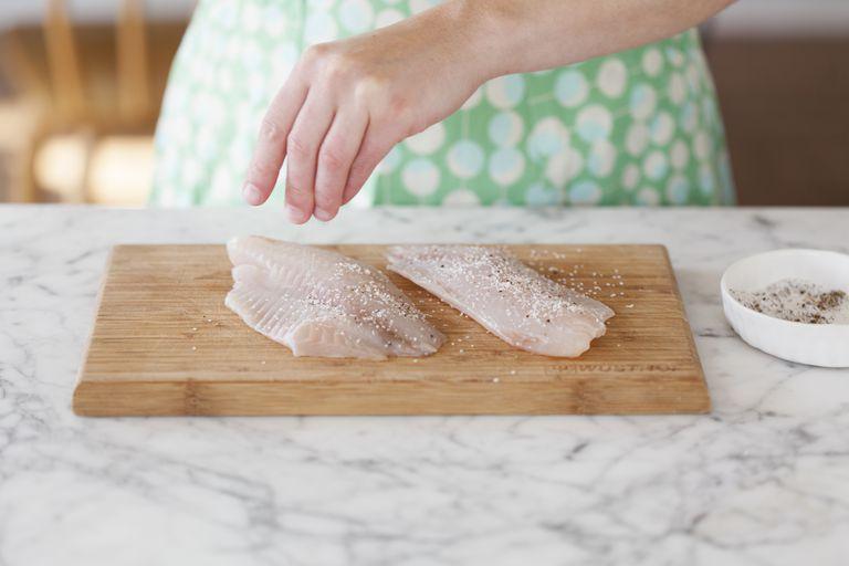 woman preparing tilapia