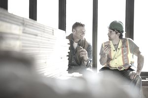 Tradesman and foreman taking lunch break at construction site