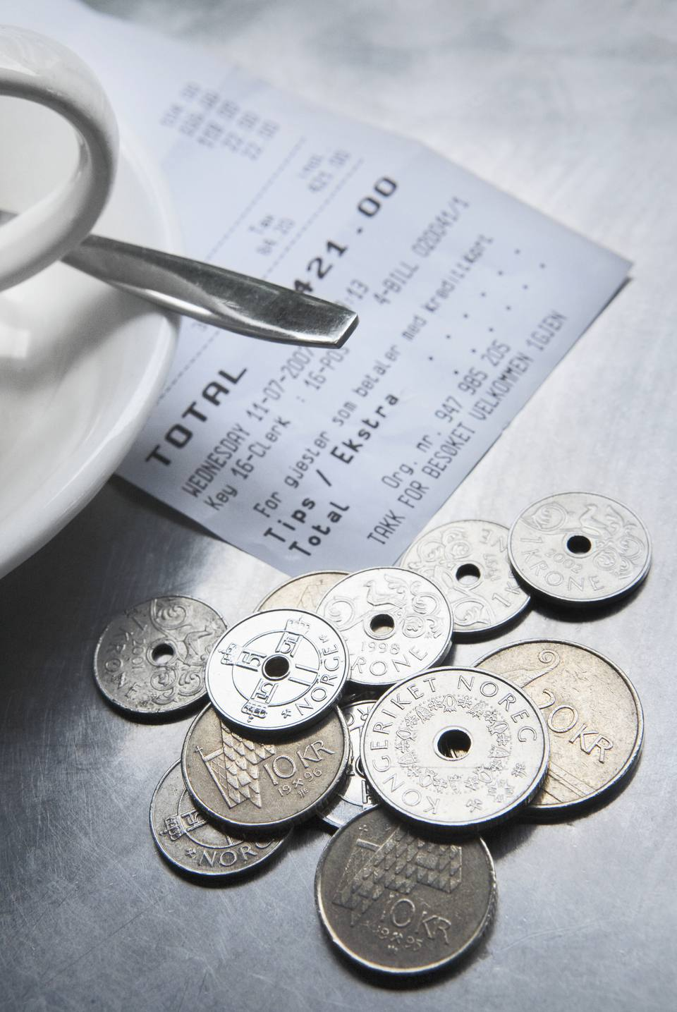 Norwegian coins with a tea cup and a saucer on a table, Oslo, Norway
