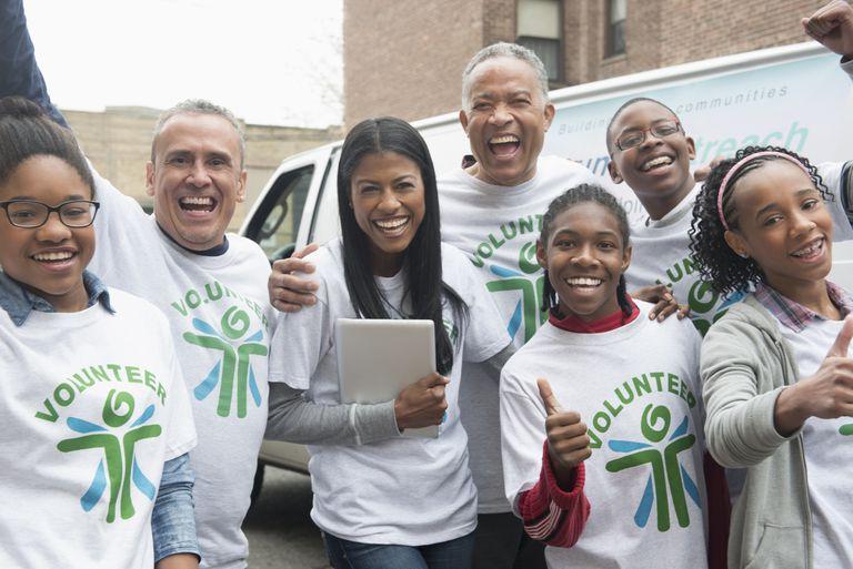 Happy volunteers near delivery van.