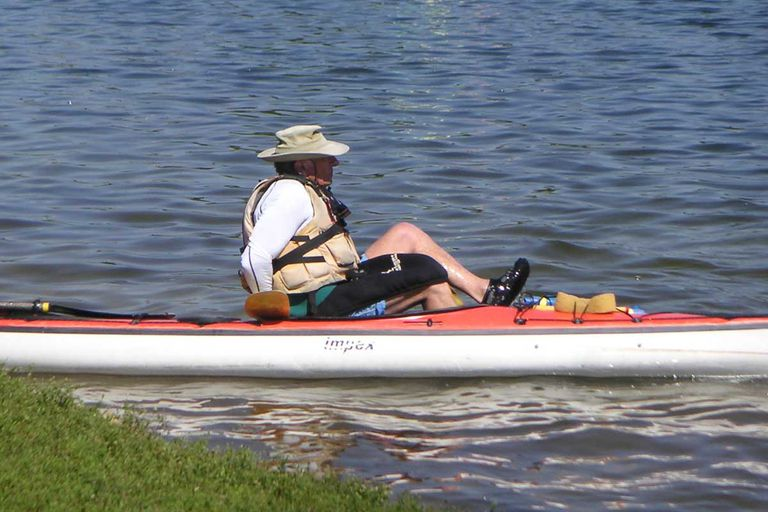 A kayak instructor demonstrates the proper way to get into a kayak.