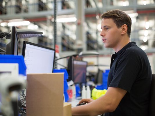 man working on computer in warehouse