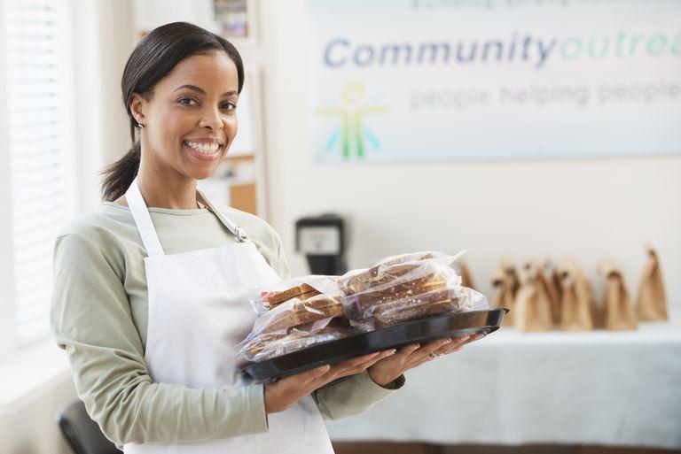 Volunteer serving sandwiches in a community kitchen.