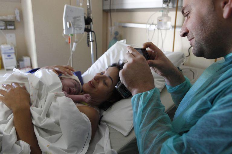 Dad taking photo of newborn at birth