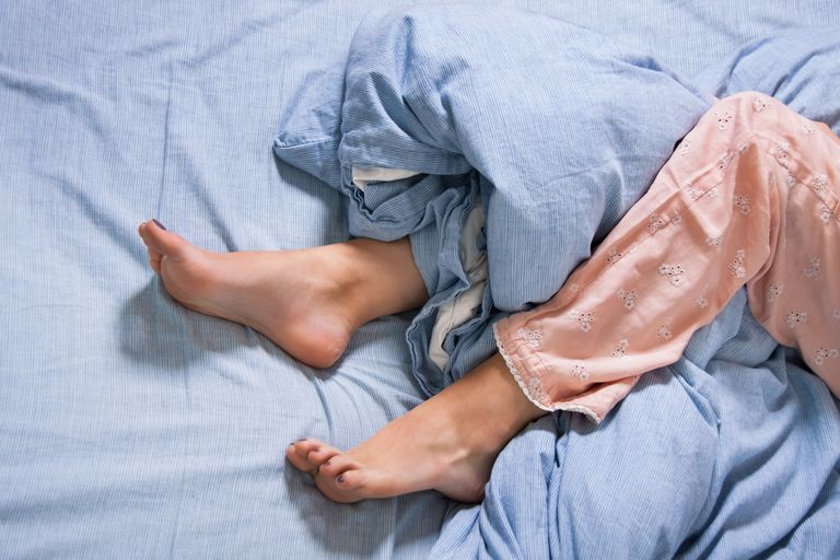 Bare Feet of a Young Woman on Blue Bed