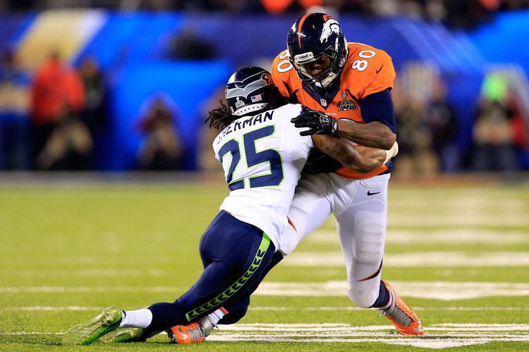 EAST RUTHERFORD, NJ - FEBRUARY 02: Tight end Julius Thomas #80 of the Denver Broncos is tackled by cornerback Richard Sherman #25 of the Seattle Seahawks during Super Bowl XLVIII at MetLife Stadium on February 2, 2014 in East Rutherford, New Jersey.