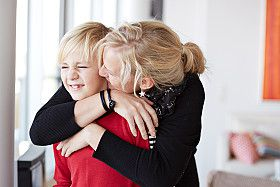 A mom hugs her son good-bye.