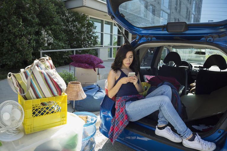College student texting and moving into college dorm