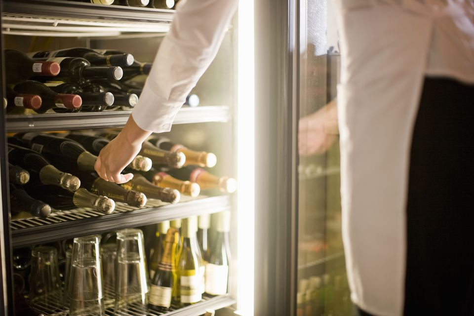 Woman reaching for bottle on wine in fridge