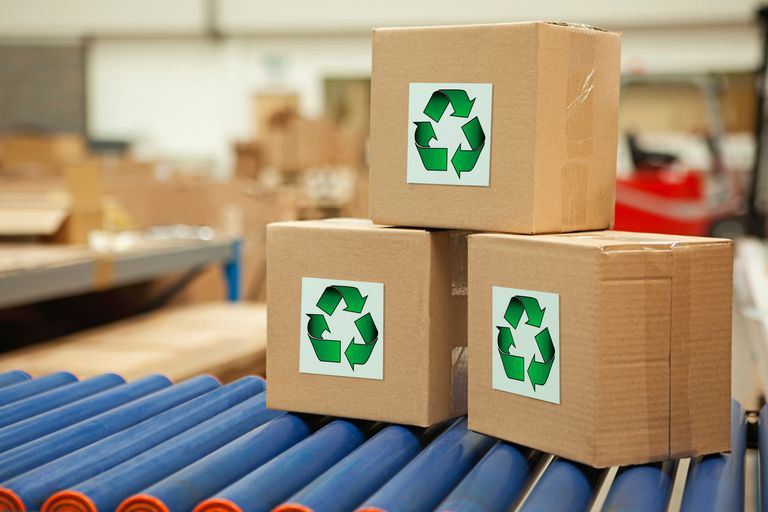 Cardboard boxes with recycling symbols on conveyor belt