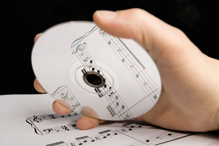 A man holding an audio CD above sheet music