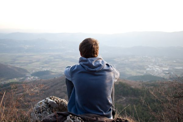 Man sitting on a hill looking out