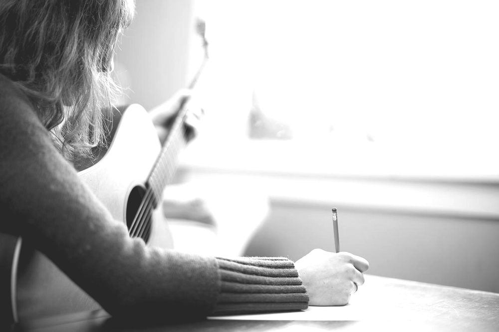 Musician Writing Song Lyrics with Guitar