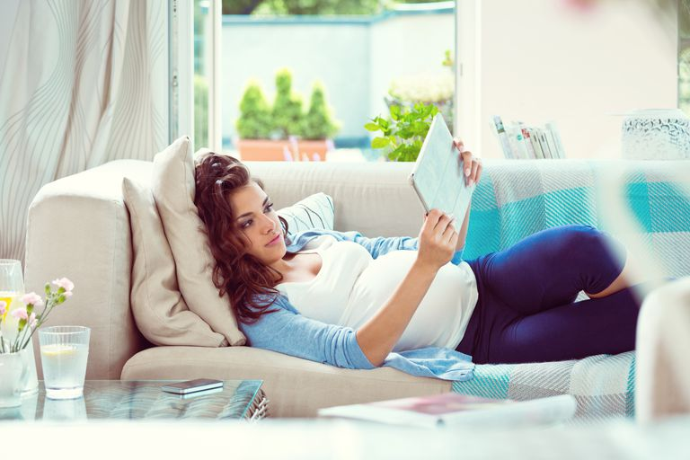Pregnant woman reading on the couch