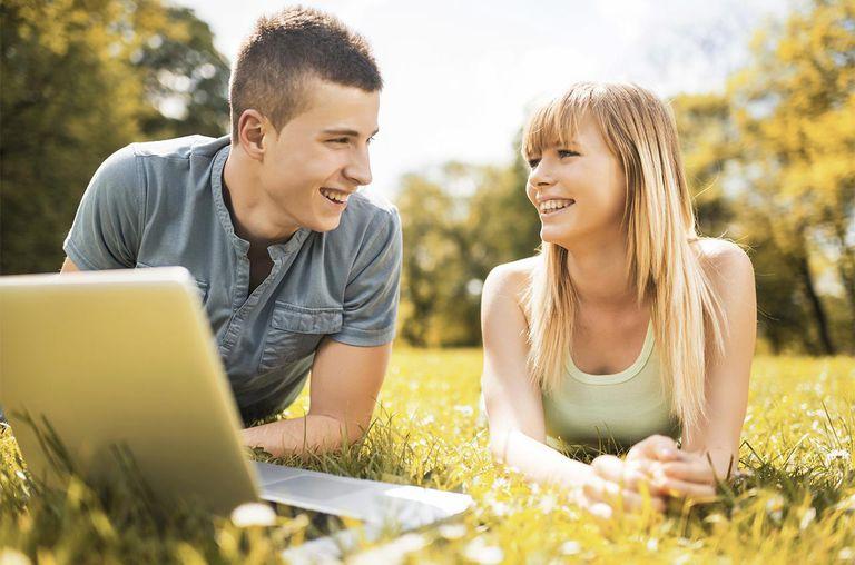 Teenage couple using laptop outdoors.