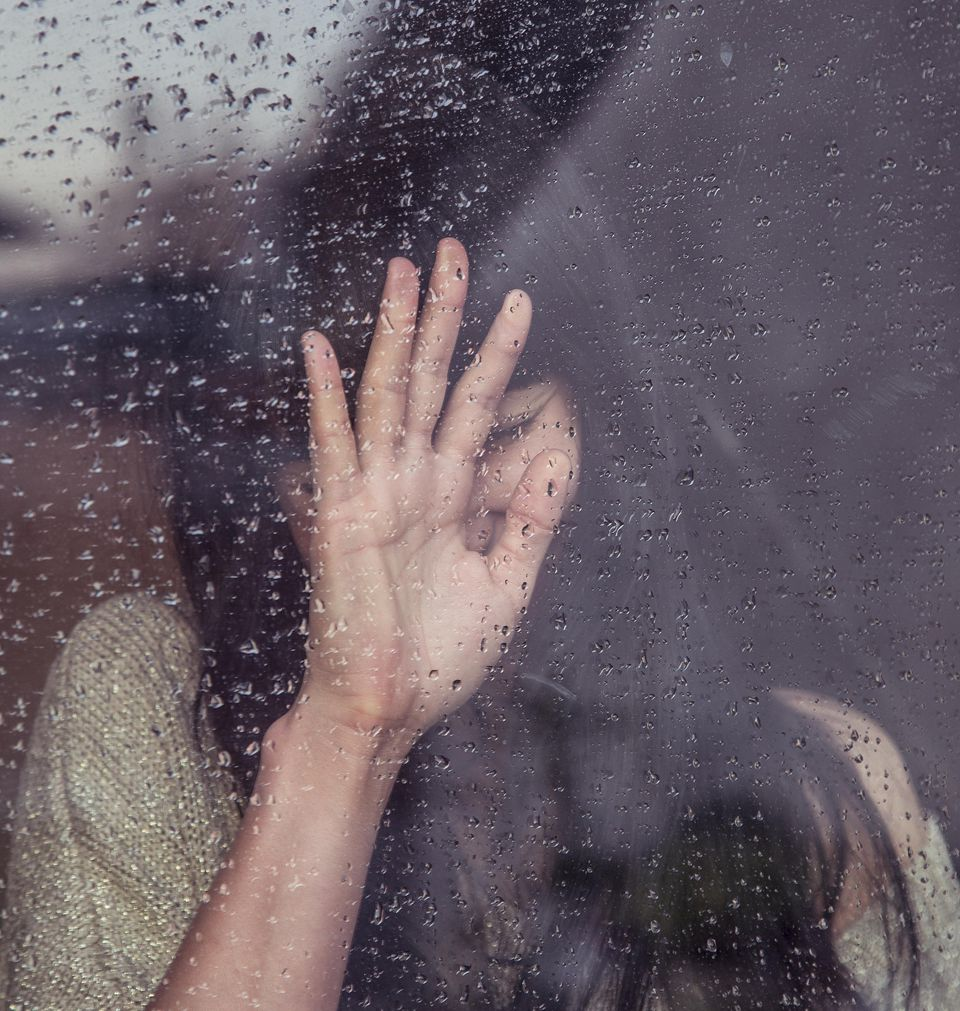 Woman leaning against rainy window