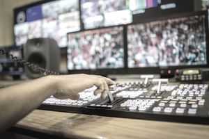 TV editor working with vision mixer in television broadcast gallery
