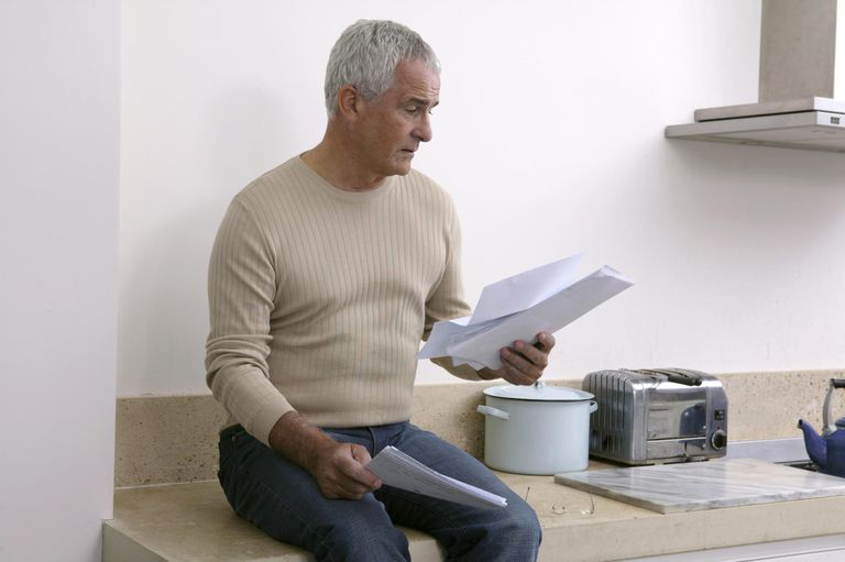 Mature man sitting on kitchen worktop, reading bills