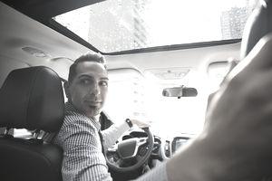 Businessman driving car looking over shoulder
