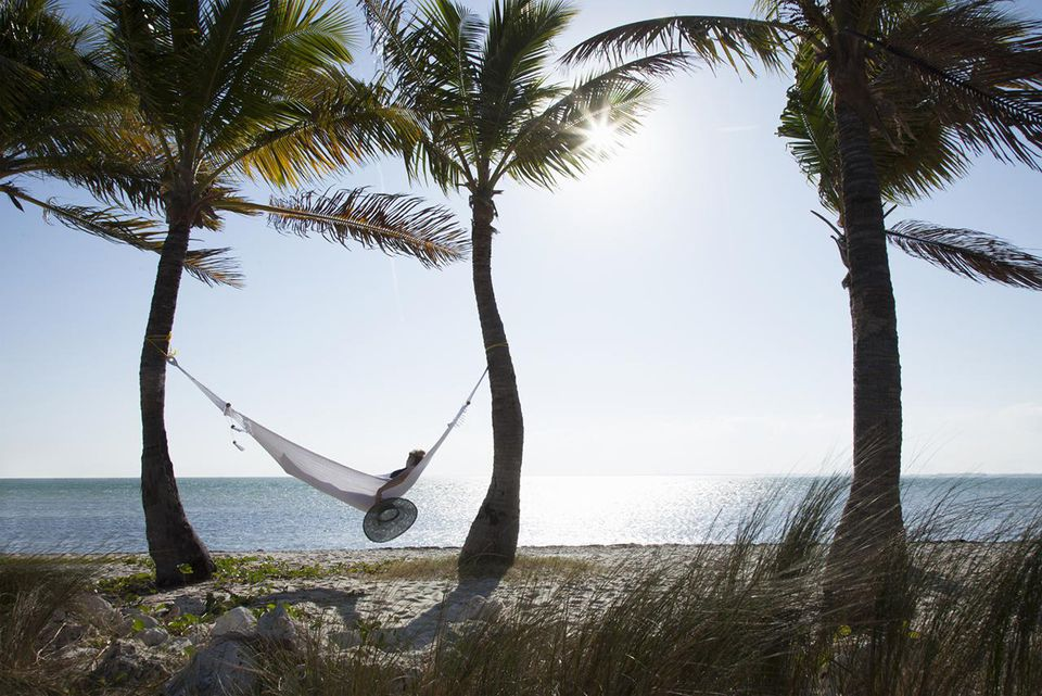Woman relaxing in a hammock on the beach