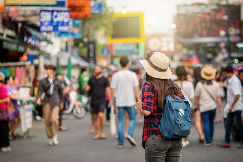 traveler and tourist concept, Back side of Young Asian traveling women walking and looking in Khaosan Road walking street in evening at Bangkok, Thailand