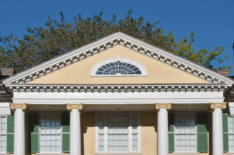detail of large triangular area outlined with dentils over portico with 4 ionic columns, a fanlight window is within the triangle