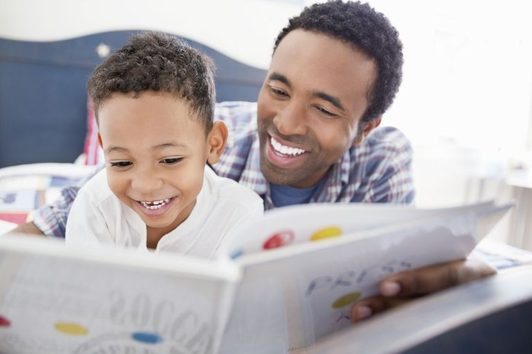 Strong single parent reading to his young son.