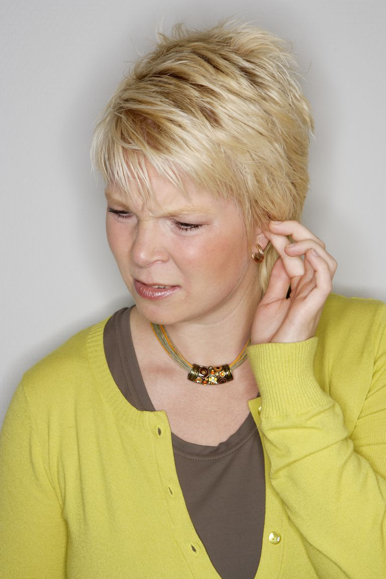 Woman looking concerned and touching ear