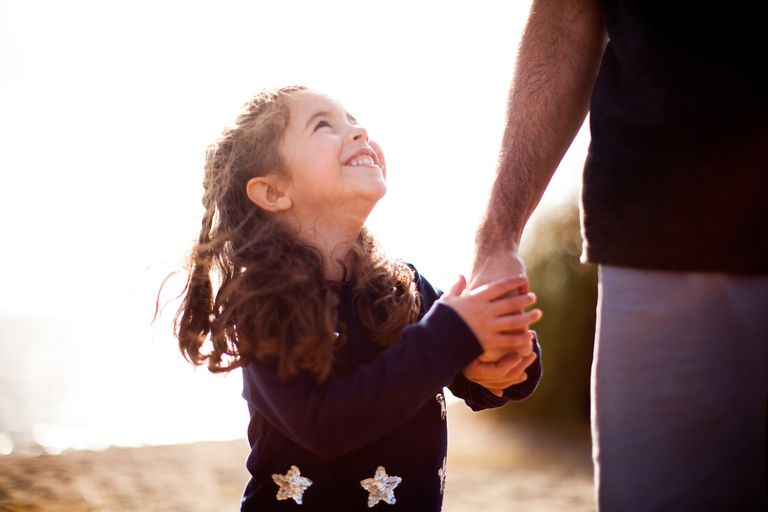 young smiling girl holding a man's hand