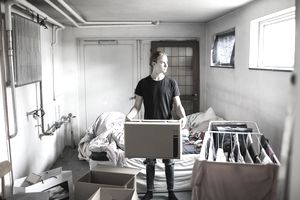 a man holding a box in an apartment