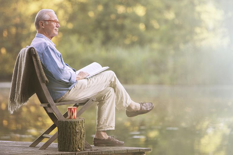 older man reading book on dock at lake