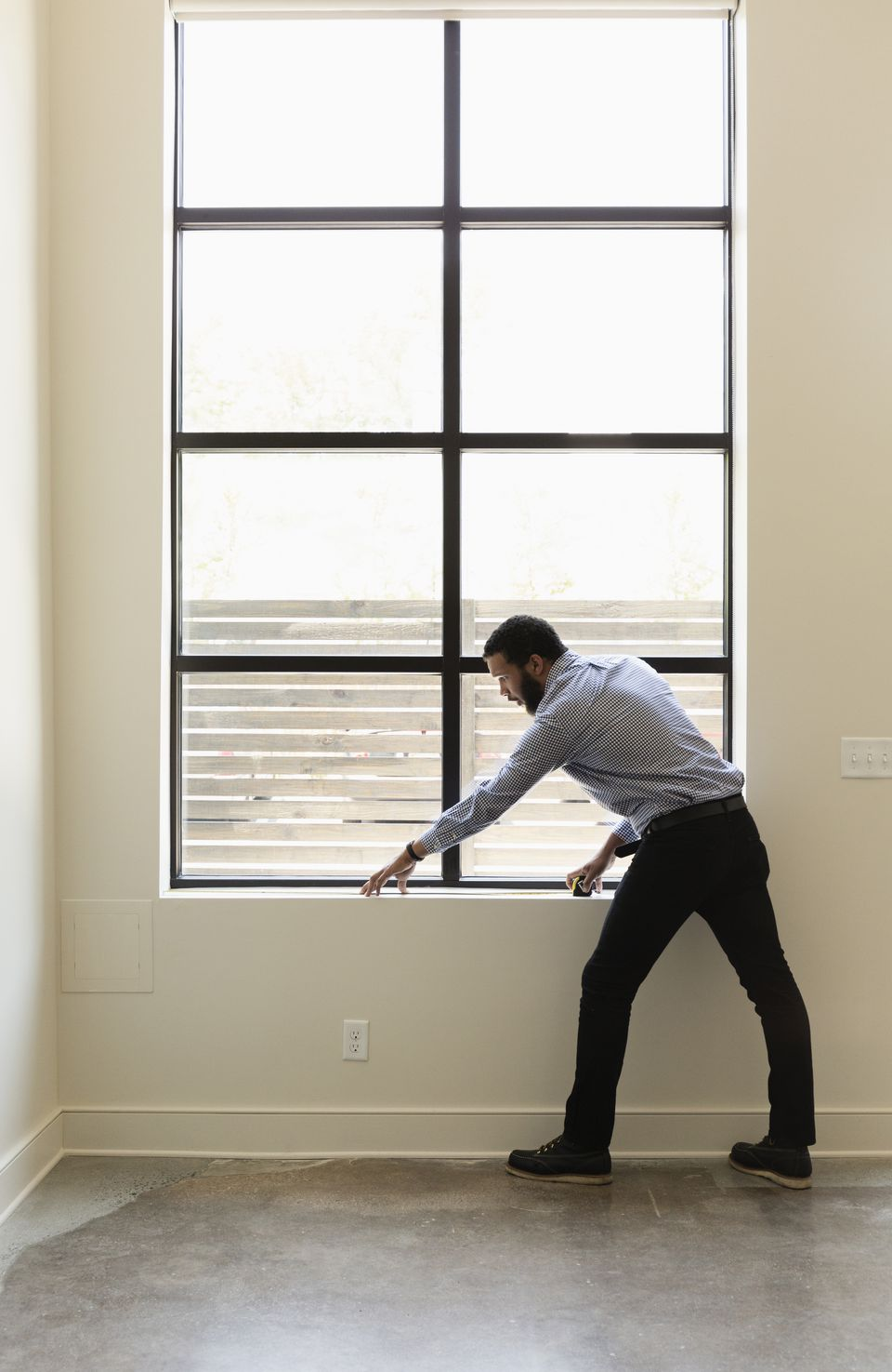 Mixed race realtor measuring window in new house