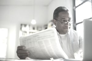 A senior man with newspaper using laptop