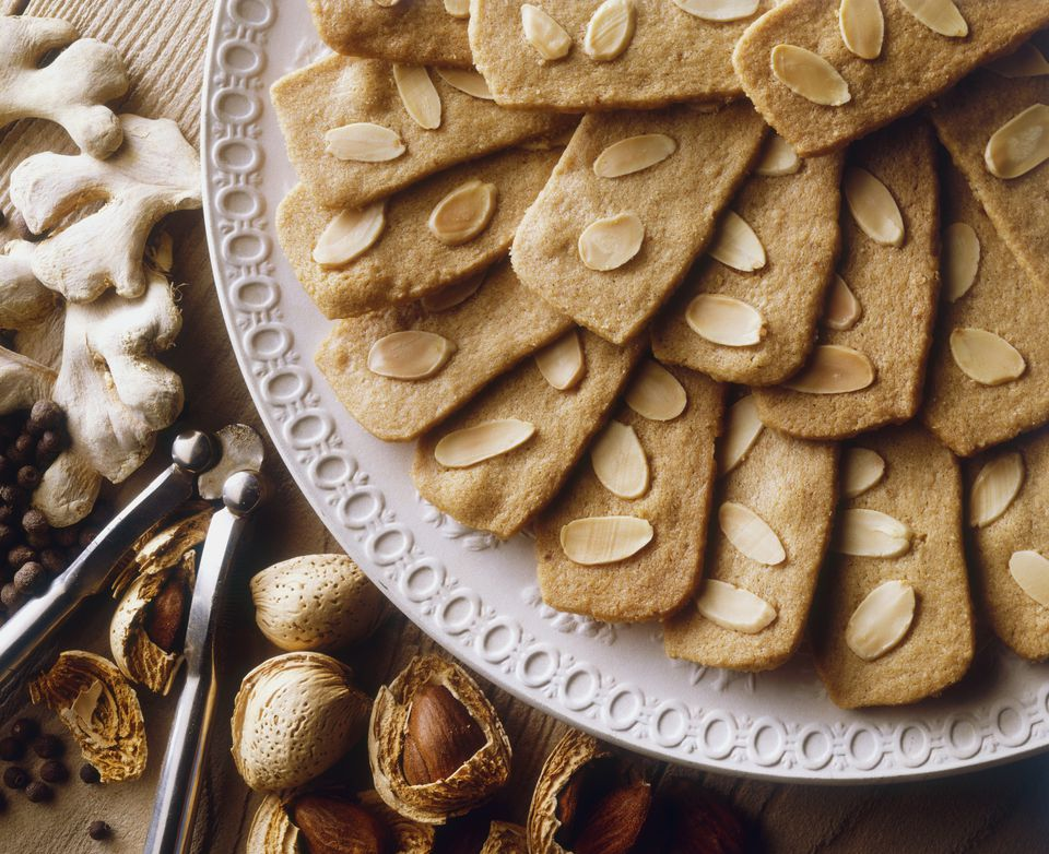 Speculaas or Spekulatius, Christmas cookies made with ginger, cinnamon and almonds, popular in Belgium and Germany, served on a plate, alongside nuts and nutcracker, view from above