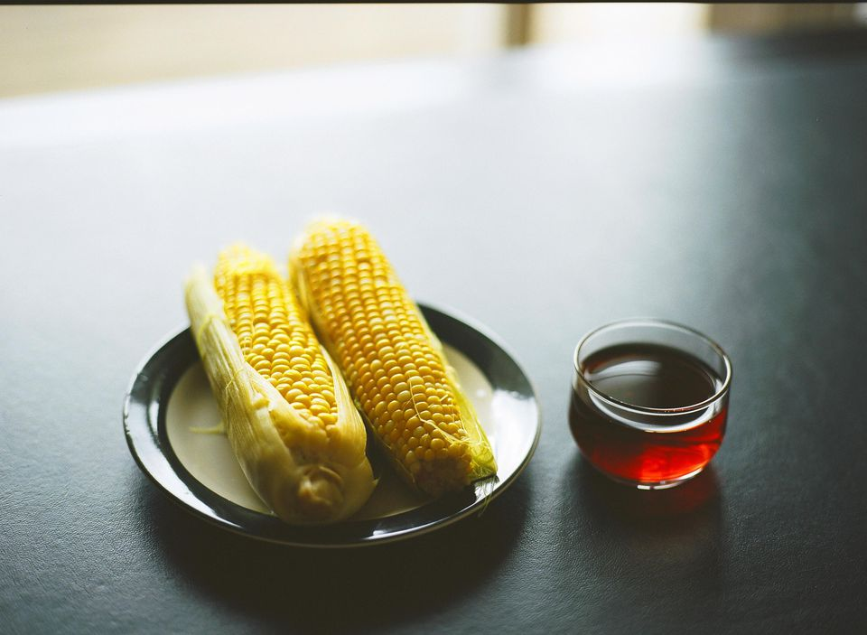 A plate of corn and a glass of corn tea