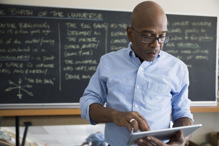 Teacher with digital tablet near blackboard in classroom