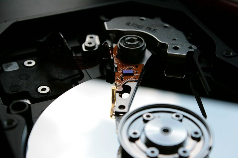 A photograph of the inside of a hard drive showing the disk and the arm that contains the needle which reads the data from the disk.