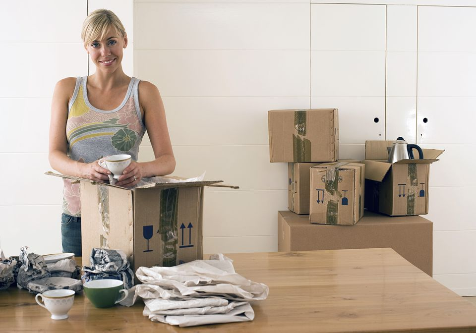 Woman packing cups into a moving box