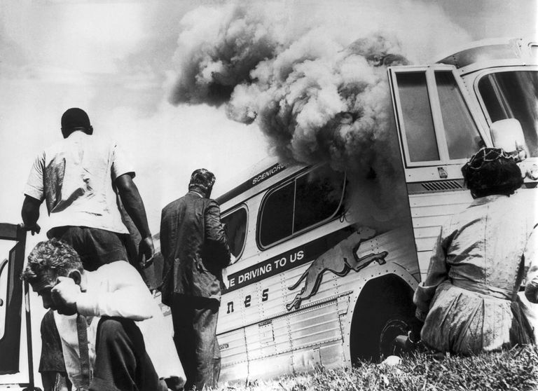 Freedom Riders on a Greyhound bus sponsored by the Congress Of Racial Equality (CORE), sit on the ground outside the bus after it was set afire by a group of whites.
