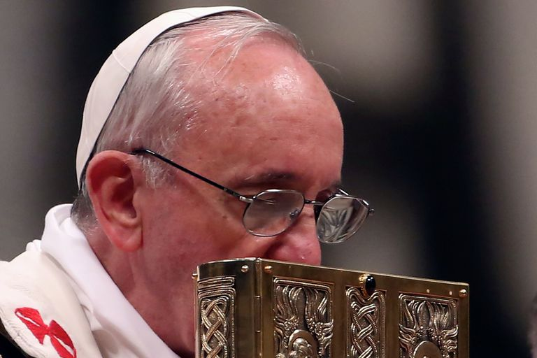Pope Francis venerates the book of the Gospels at Easter Vigil Mass at St. Peter's Basilica, March 30, 2013. (Photo by Franco Origlia/Getty Images)