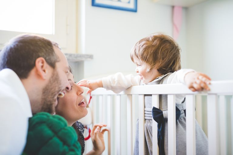 Mid adult couple laughing with toddler daughter in crib